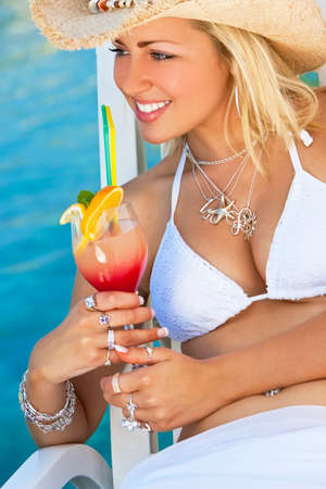 Stunningly beautiful young blond woman in straw cowboy hat and white bikini enjoying a cocktail by a turquoise blue sea Stock Photo