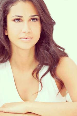Studio portrait of a beautiful young Latina Hispanic young woman or girl looking thoughtful photo