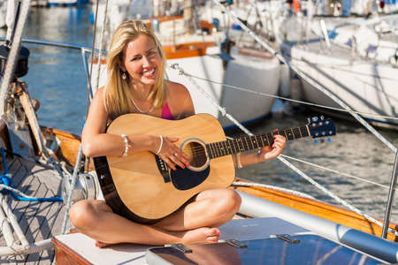 A beautiful blond young woman sitting on the deck of sail boat or yacht in natural golden summer sunshine having fun playing her guitar Stock Photo