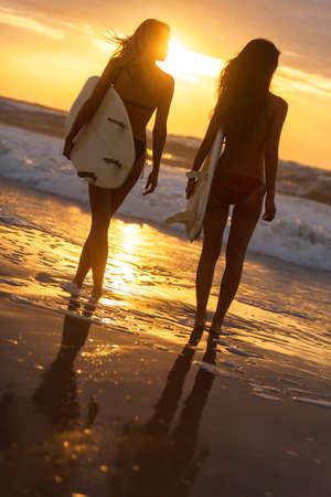 sexy young girls: Вид сзади двух красивых секси молодой женщины серфер девушки в бикини с белыми досками для серфинга на пляже на закате или восходе солнца