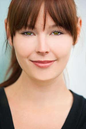 ojos verdes: Retrato de una mujer joven feliz o niña con el pelo negro, ojos verdes y una hermosa sonrisa.