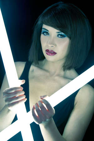 A stunningly beautiful young Asian Chinese woman holding glowing fluorescent tubes in a night club