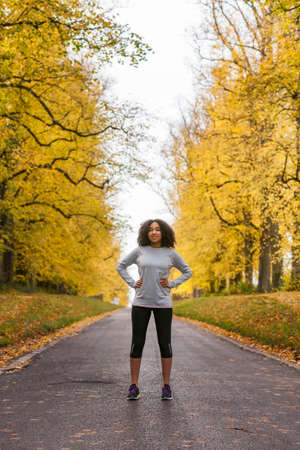 happy african: Beautiful mixed race African American young woman girl teenager fitness running jogging in Autumn Fall trees
