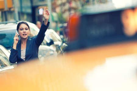 taxi: Una mujer joven o mujer de negocios llamando a un taxi amarillo mientras habla por su teléfono celular en una ciudad de Nueva York