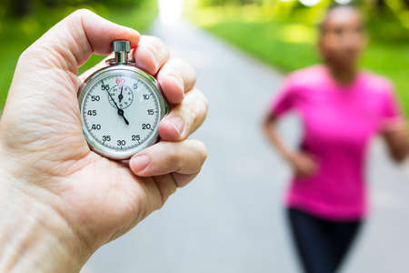 Classic stopwatch timer and young woman in pinkl running or jogging being timed on a road in summer Banco de Imagens