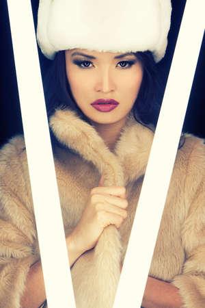 tubos fluorescentes: Joven y bella mujer asi�tica japonesa o ni�a iluminada por brillantes tubos fluorescentes y el uso de (falsa) sombrero de piel y el pelaje Foto de archivo