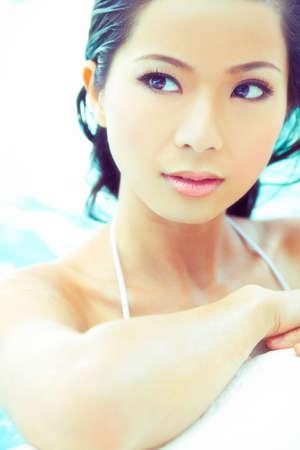 schöne augen: schöne sexy junge chinesische Asian Oriental Frau einen Bikini und entspannt auf der Seite eines Schwimmbades zu tragen.