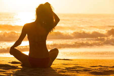 A relaxed sexy young brunette woman or girl wearing a bikini sitting on a deserted tropical beach at sunset or sunrise Stock Photo