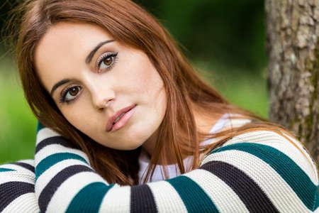 ojos marrones: Retrato al aire libre de la hermosa muchacha triste o reflexiva mujer joven con el pelo rojo que lleva un puente a rayas sentado y apoyado en un árbol en el campo Foto de archivo