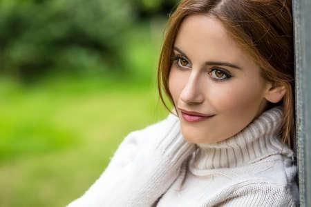 ojos verdes: Retrato al aire libre de la hermosa chica reflexiva o una mujer joven con el pelo rojo llevaba un suéter blanco