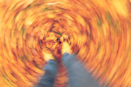 motion blurred photograph of man or womans feet walking through golden Fall or Autumn leaves Фото со стока