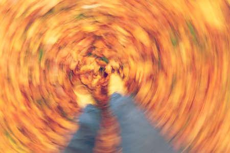 Movimiento borrosa fotografía del hombre o de los womans pies caminando a través de la caída de oro o de las hojas de otoño Foto de archivo - 65695134