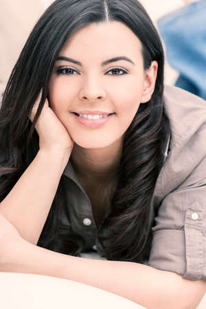 brown eyes: Portrait of a beautiful young Latina Hispanic woman smiling laying down and relaxing at home on a sofa Stock Photo
