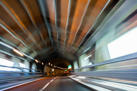 speed car: Motion blur driving a car at speed through a road tunnel Stock Photo