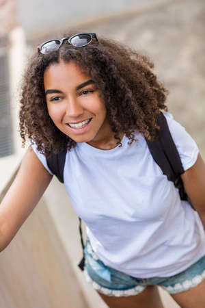 back pack: Outdoor portrait of beautiful happy mixed race African American girl teenager female young woman smiling with perfect teeth wearing shorts, t-shirt and back pack