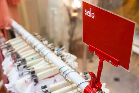 bargaining: A red sale sign on rail of clothes in a shop