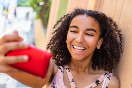 perfect teeth: Beautiful happy mixed race African American girl teenager female child smiling with perfect teeth taking selfie photograph with cell phone