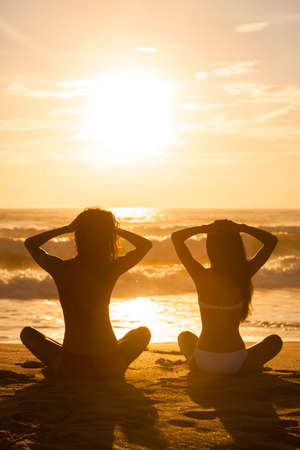 woman sunset: Two relaxed sexy young women or girls wearing bikinis sitting on a deserted tropical beach at sunset or sunrise