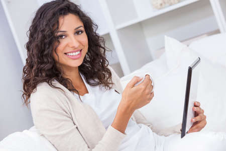 sexy latina: Beautiful young Latina Hispanic woman smiling, relaxing and drinking a cup of coffee or tea using tablet computer