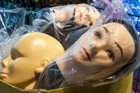 male mannequin: Mannequin shop dummy heads in plastic bags waiting for display