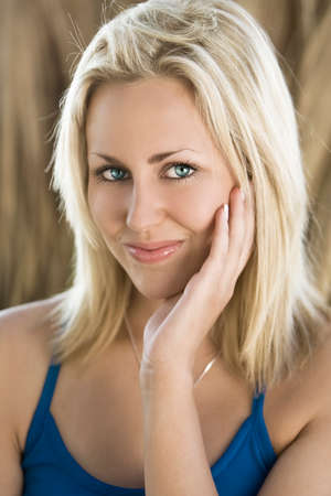 blond haired: Exterior portrait shot of a happy smiling beautiful blond haired female model with stunning blue eyes.