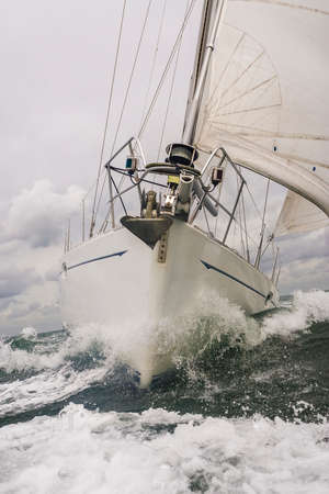 Close up on the bow of a sailing boat or yacht breaking through a wave on a stormy sea Фото со стока