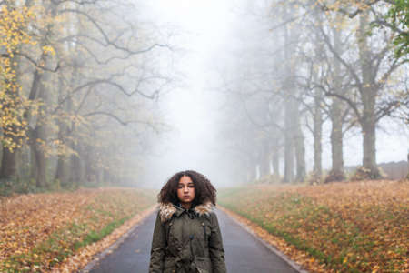 depressed: Beautiful mixed race African American girl teenager female young woman standing outside on a road in autumn or fall looking sad depressed or thoughtful