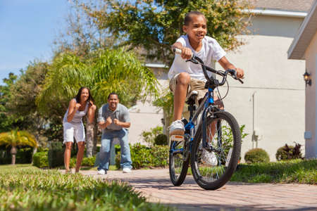 A young African American family with boy child riding his bicycle and his happy excited parents giving encouragement behind him photo