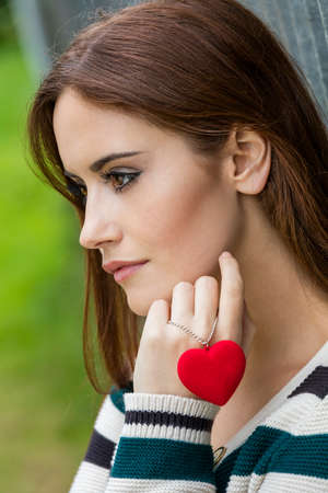 beautiful sad: Beautiful thoughtful sad heartbroken girl or young woman with red hair holding a red heart necklace