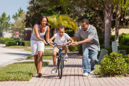 A young African American family with boy child riding his bicycle and his happy excited parents giving encouragement next to him photo