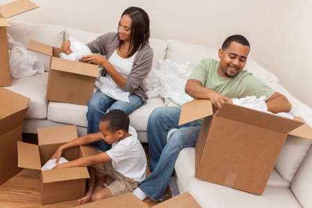African American family, parents and son, adults and child, unpacking boxes and moving into a new home. photo