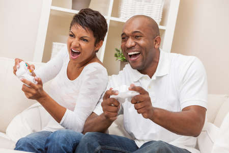 battle of the sexes: African American couple, man and woman, having fun playing video console games together.