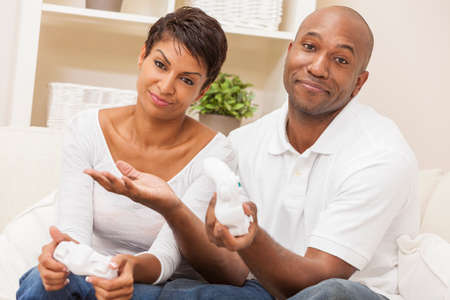 sexes: African American couple, man and woman, having fun playing video console games together. The woman has just beaten the man, she is celebrating, he is resigned. Stock Photo