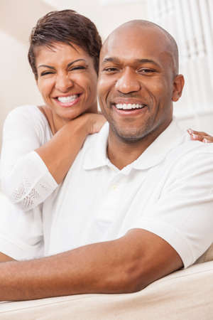 perfect teeth: A happy smiling African American man and woman couple with perfect teeth, in their thirties sitting at home