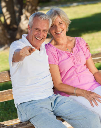 Happy senior man and woman couple sitting together laughing and pointing on a park bench outside in sunshine photo