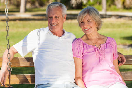 Happy senior man and woman couple sitting together on a park bench outside in sunshine photo