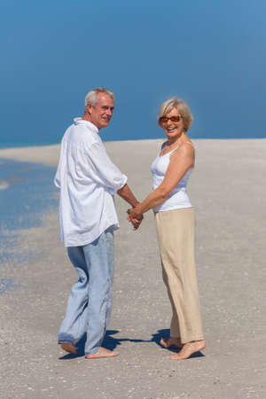 Happy senior man and woman couple walking and holding hands on a deserted tropical beach with bright clear blue sky photo