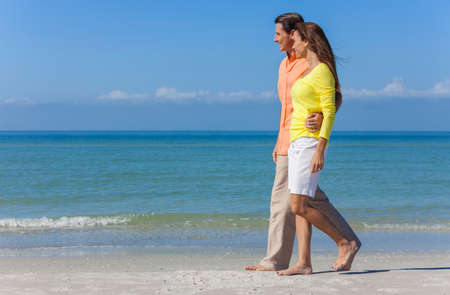 romantic sky: Man and woman romantic couple in colorful clothes walking on a deserted tropical beach with bright clear blue sky Stock Photo