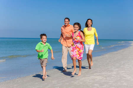 A happy family of mother, father and two children, son and daughter, running and having fun in the sand of a sunny beach photo