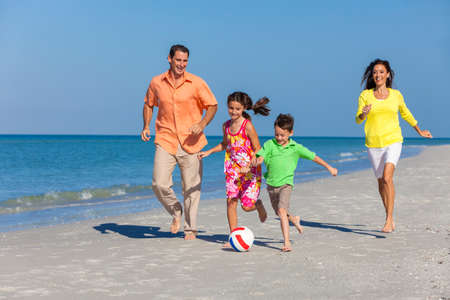 A happy family of mother, father and two children, son and daughter, running playing soccer or football in the sand of a sunny beach photo