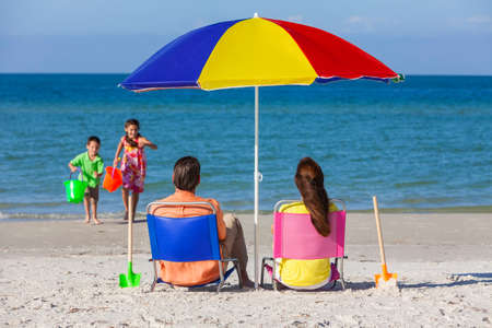 Rear view of a happy family of mother & father, parents daughter & son children having fun in deckchairs under an umbrella on a sunny beach photo