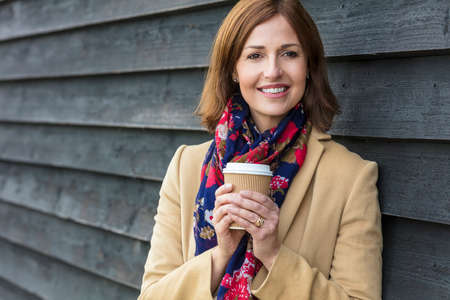 successful woman: Portrait shot of an attractive, successful and happy middle aged woman female outside drinking coffee in a disposable takeaway cup. Stock Photo