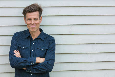 arms folded: Portrait shot of an attractive, successful and happy middle aged man male arms folded outside wearing a blue denim shirt