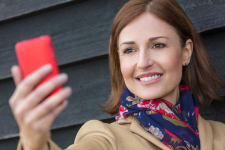Attractive, successful and happy middle aged woman female taking selfie photograph on mobile cell phone