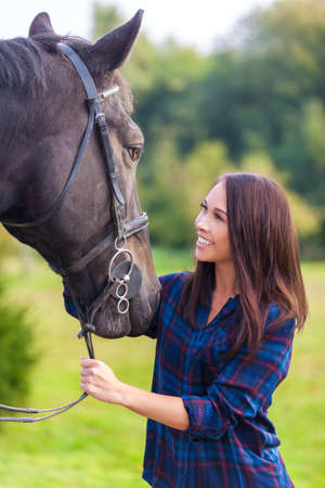 young asian: Beautiful happy smiling Asian Eurasian young woman or girl wearing plaid checked shirt with her her horse in sunshine Stock Photo