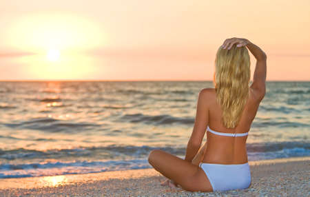 A relaxed sexy young blonde woman or girl wearing a bikini sitting on a deserted tropical beach at sunset or sunrise Stock Photo