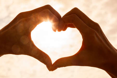 Silhueta de forma de coração de mão feita contra o sol e o céu de um nascer ou pôr do sol Foto de archivo