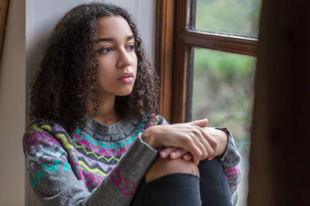 Beautiful mixed race African American girl teenager female young woman sad depressed or thoughtful looking out of a window