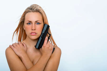 Beautiful young woman with a handgun or pistol gun photo
