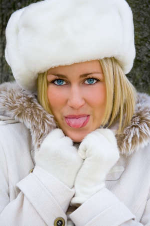 Beautiful Blond Young Woman Girl in White Fake Fur Hat and Coat Sticking Out her Tongue photo